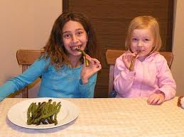 "This picture is bullshit.  You can clearly see the girl in blue is saying ""hurry the hell up and take the picture because this piece of asparagus is so gross and the girl in pink isn't even trying to pretend."
